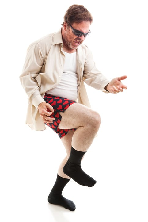 Fifty year old man in his underwear and sunglasses playing air guitar.