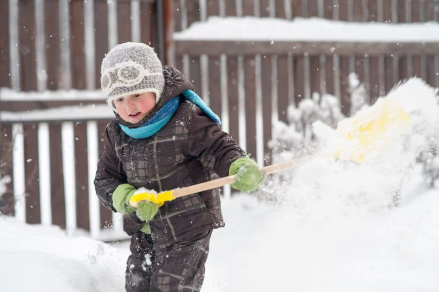 Little boy shovels snow
