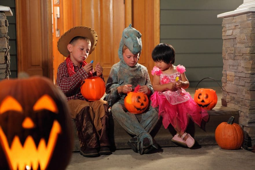 Three children in Halloween costumes sitting on porch