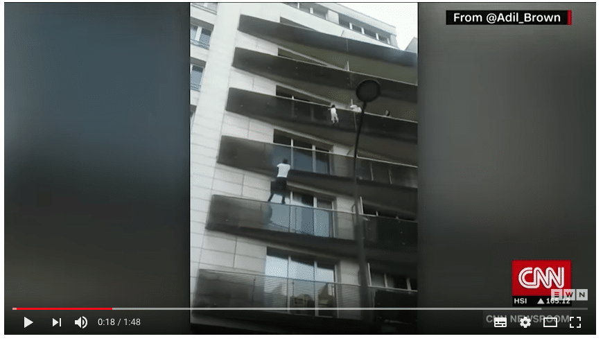 Image of a man climbing a building trying to save a kid on a balcony