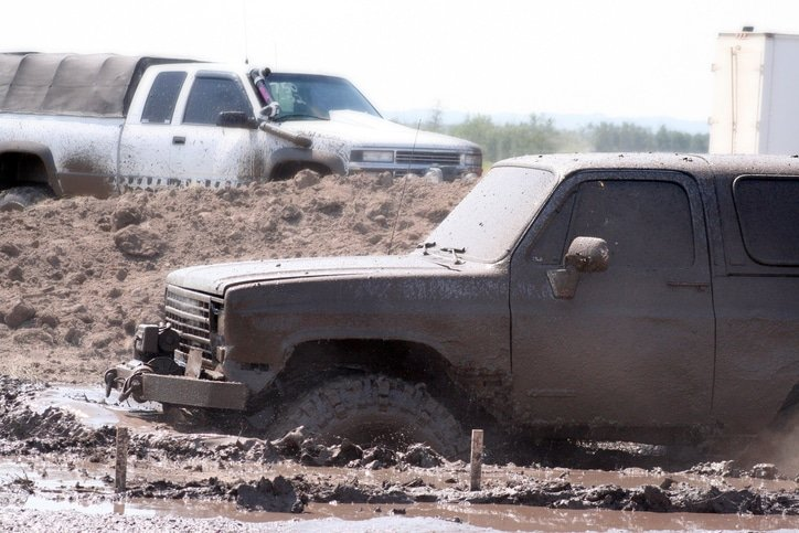 Big 4x4 pushes its way through the mud in a mud bog.