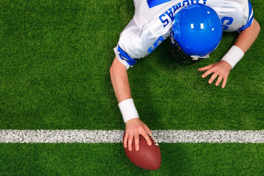 Overhead photo of an American football player making a one handed touchdown.